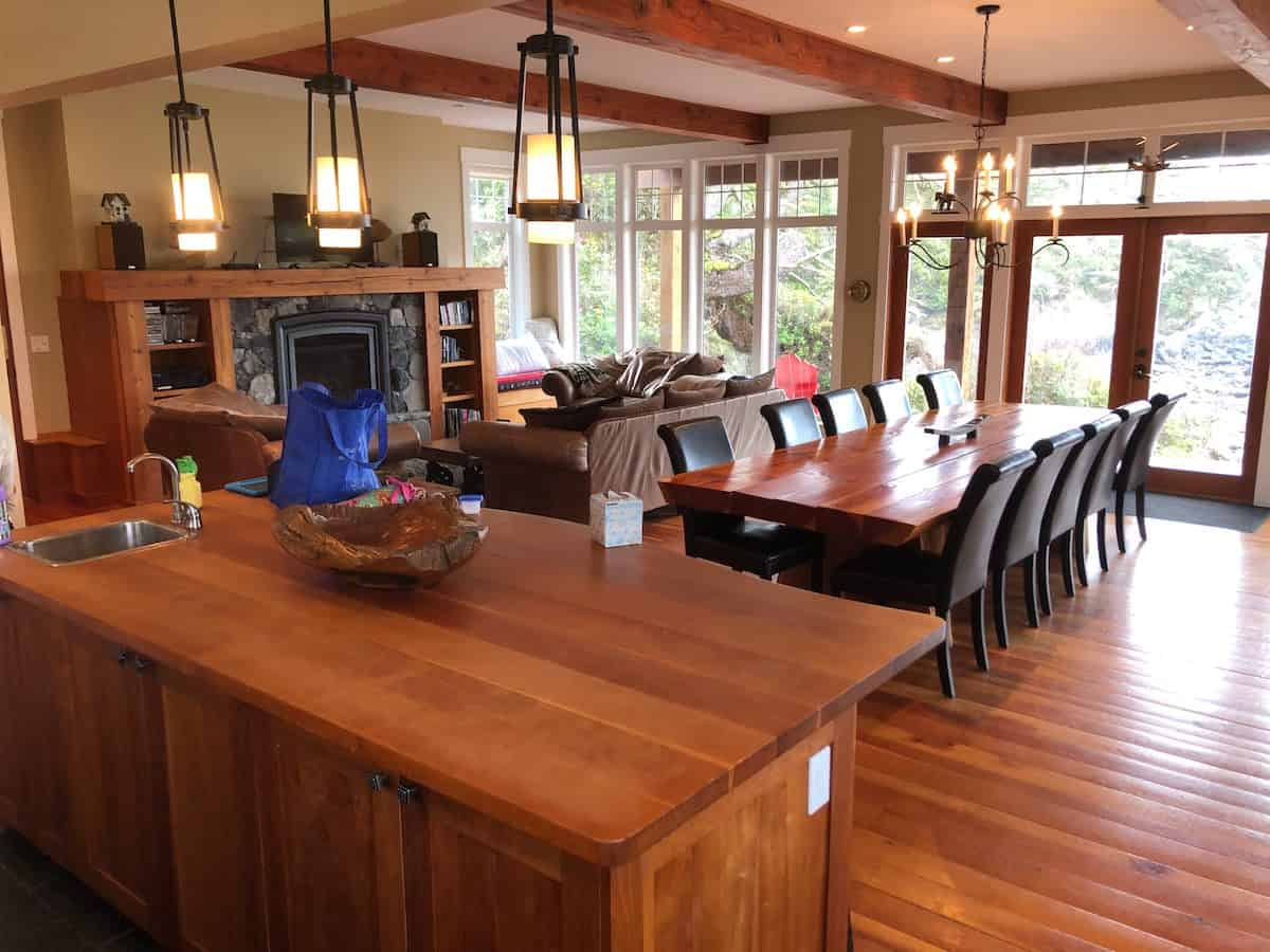 This great room houses the living room, dining area and kitchen all on the same hardwood flooring that blends well with the kitchen island, dining table and the wooden beams that houses the fireplace. This is across from the brown leather sofa set.