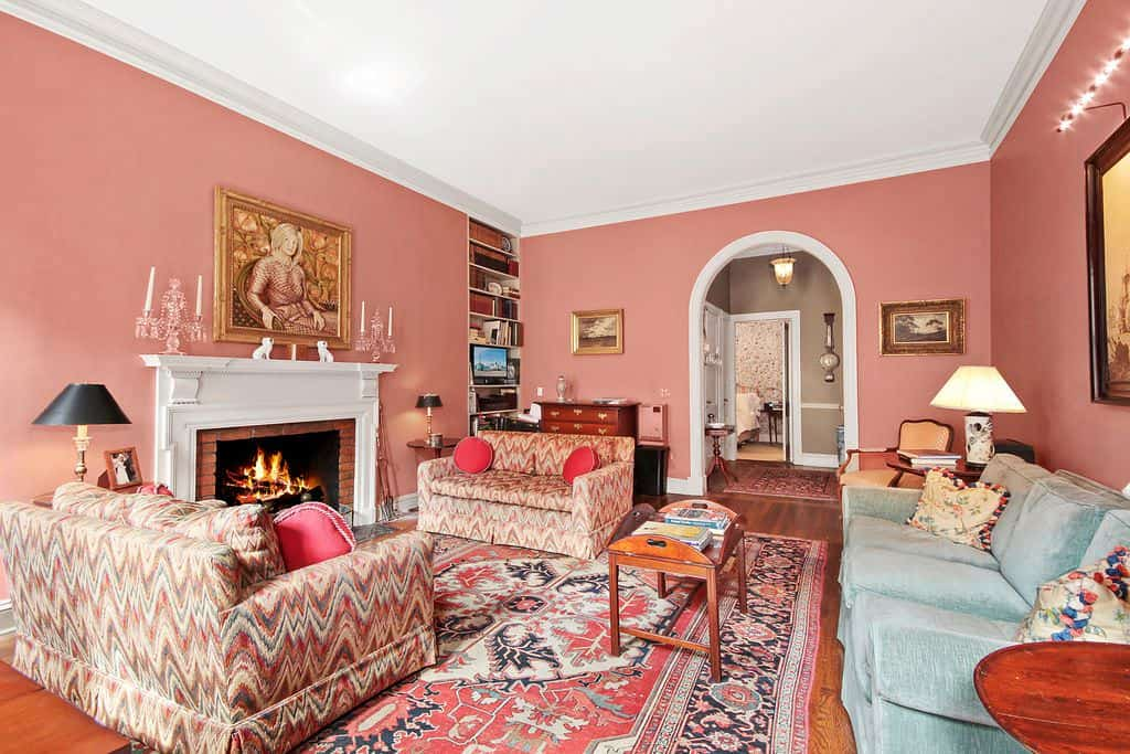 The lovely pink walls of this living room matches well with the pink patterned area rug of the hardwood flooring and the patterned cushions of the tow sofas flanking the fireplace with a white mantle. This mantle is topped with a classic painting.