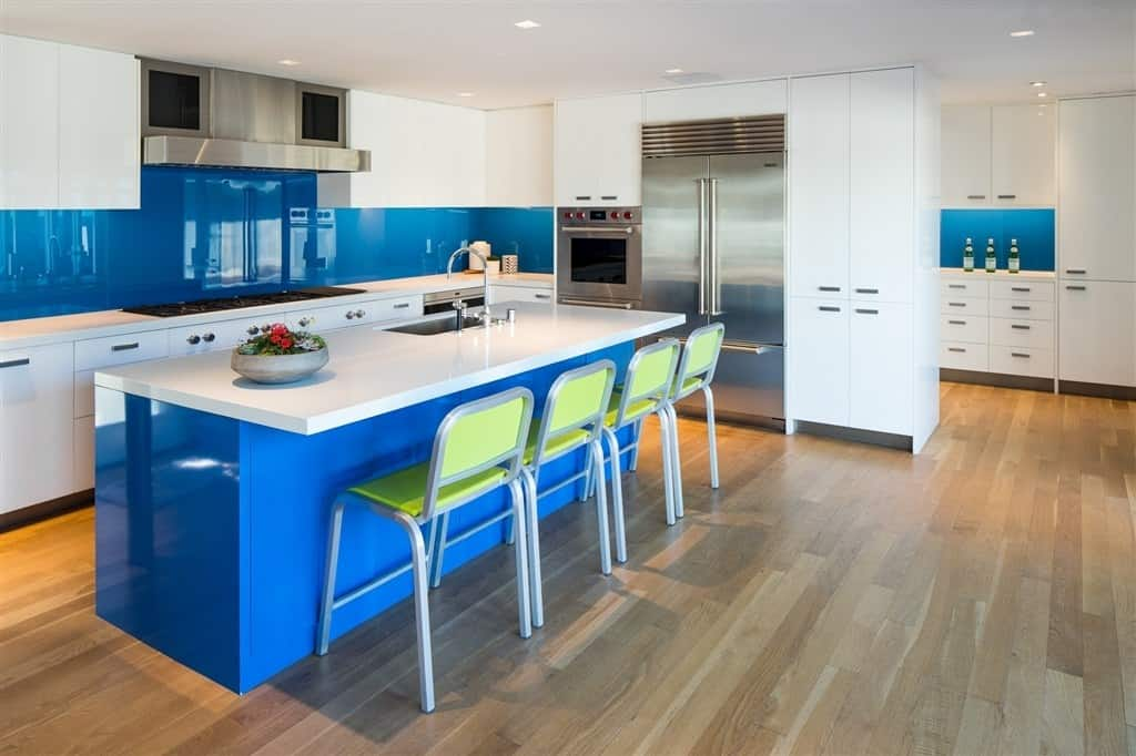 Stylish kitchen with polished blue accents, hardwood floors, breakfast island, white countertops, white custom cabinets, and stainless steel appliances.