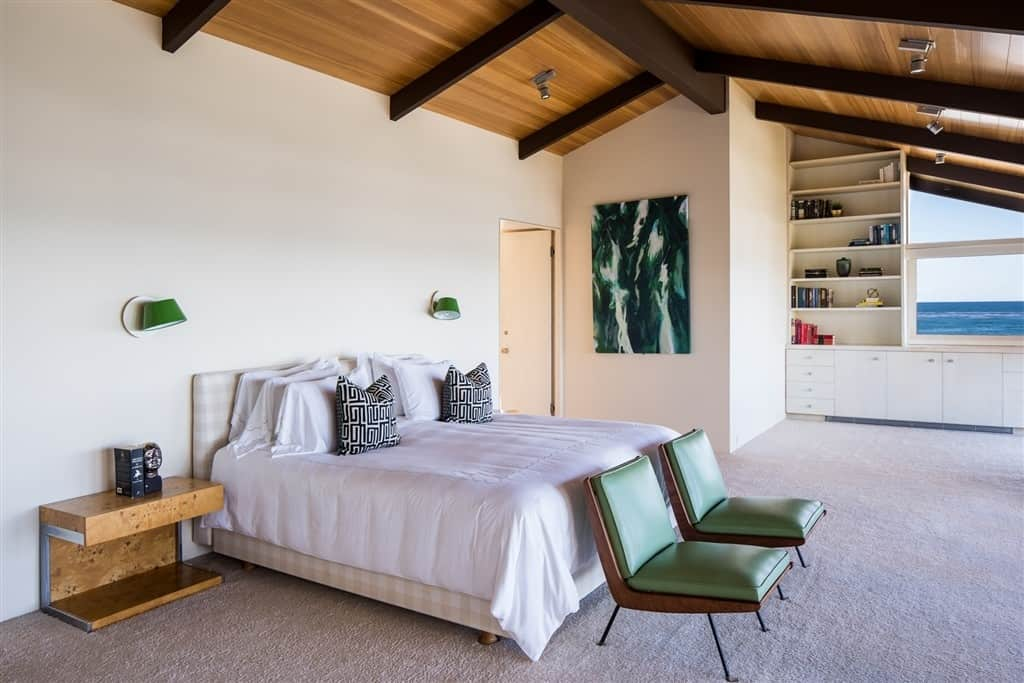 Large mid-century modern primary bedroom featuring a bed with a classy frame, along with stylish green wall sconces that match a couple of green seats at the edge of the bed.
