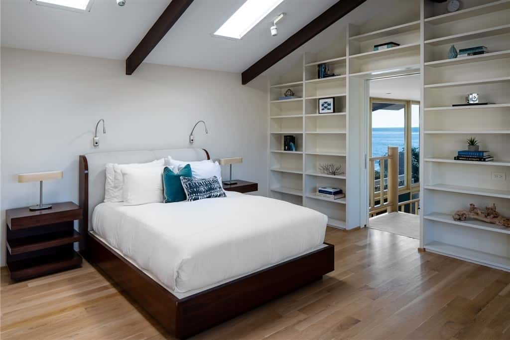 A mid-century modern primary bedroom featuring white walls and hardwood floors, along with built-in shelves and a ceiling featuring skylights.