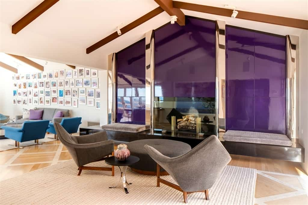 Mid-century modern living room with two seating areas and a glass enclosed fireplace fixed on the purple accent wall that's framed with chrome columns.