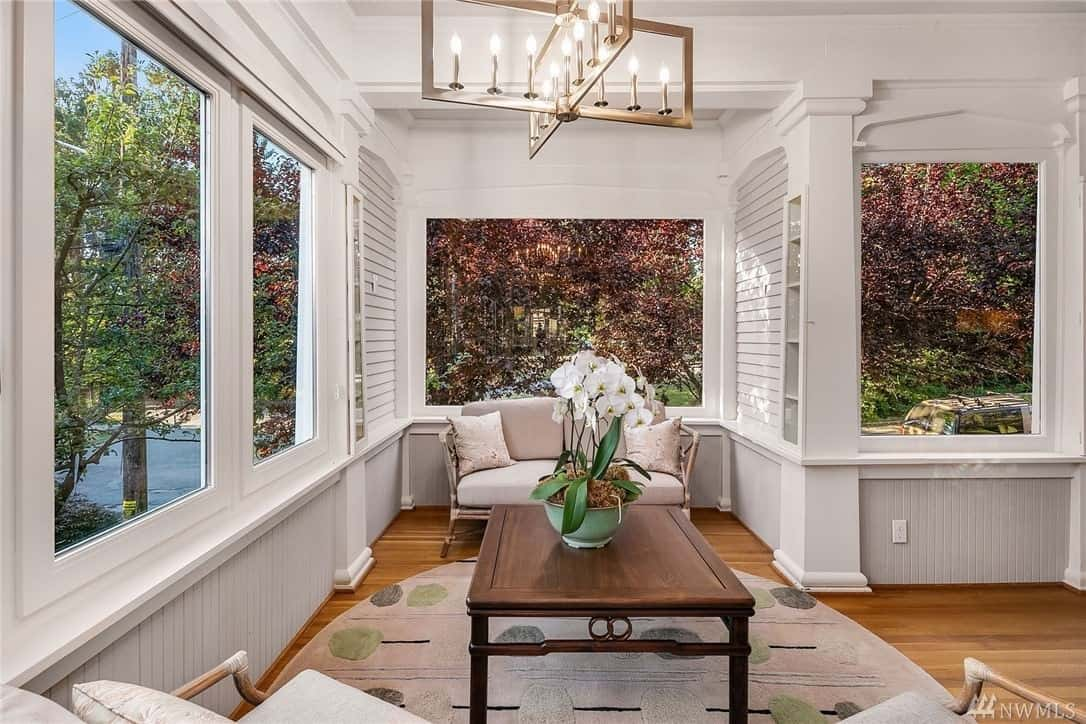 Elegant sunroom with hardwood flooring, comfortable chairs and large picture windows on all sides in an older remodelled house.