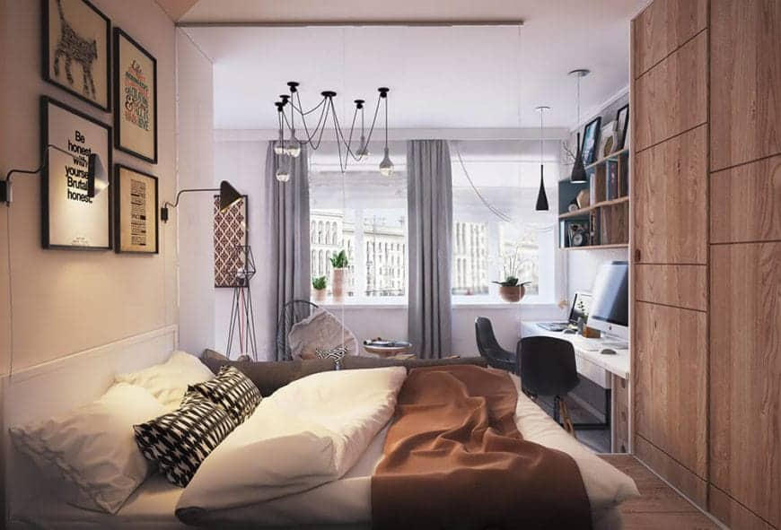 This is a Scandinavian-Style bedroom that is built into a nice and cozy alcove that gives you a feeling of an embrace. The wooden wall at the foot of the white bed has built-in cabinets and drawers that make it seem whole. There are wall-mounted artworks above the white headboard.