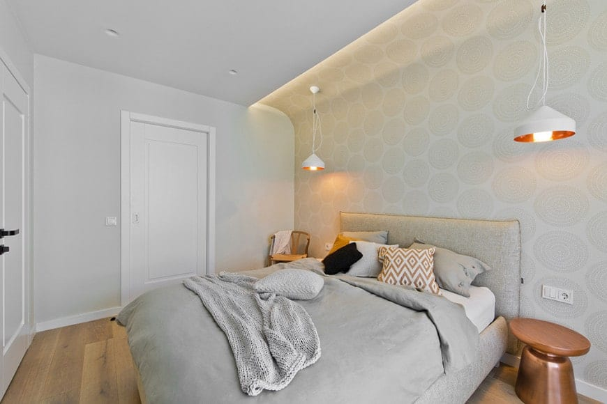 This simple bedroom has a muted white hue to it with its light gray bedsheets and a chic patterned wallpaper behind the gray cushioned headboard. The bed is flanked by two white pendant lights hanging from the white ceiling.
