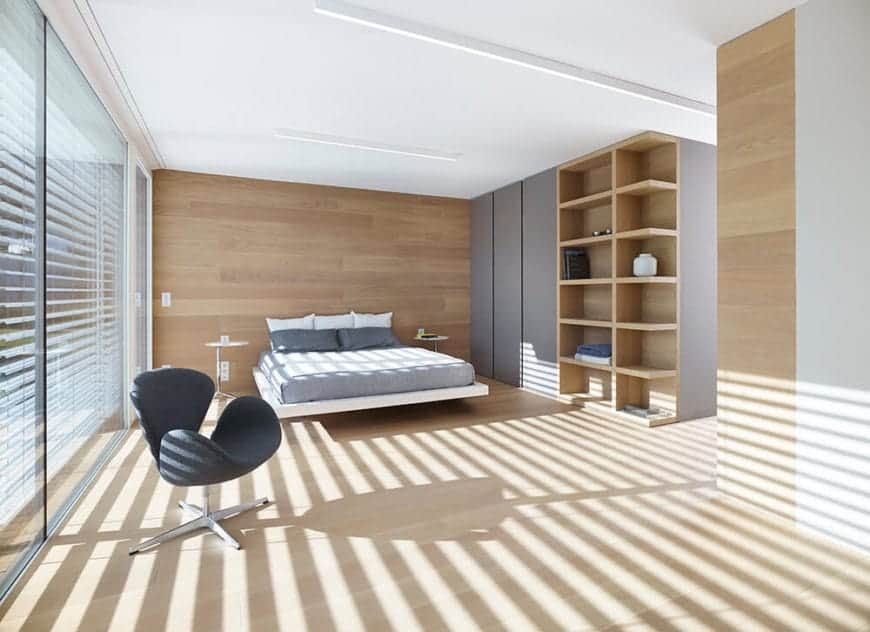 This Scandinavian-Style master bedroom has a bed on a floating platform that is attached to a wooden wall flanked by two modern bedside tables. It has glass walls on one side and on the other is a huge wooden structure that has built-in cabinets and shelves.
