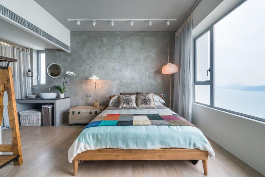 The wooden bedframe stands out against the white hardwood flooring, gray ceiling and walls. Beside the bed is a wooden chest that doubles as a bedside table. Next to it is a vanity area built into the gray wall with faucet and sink.
