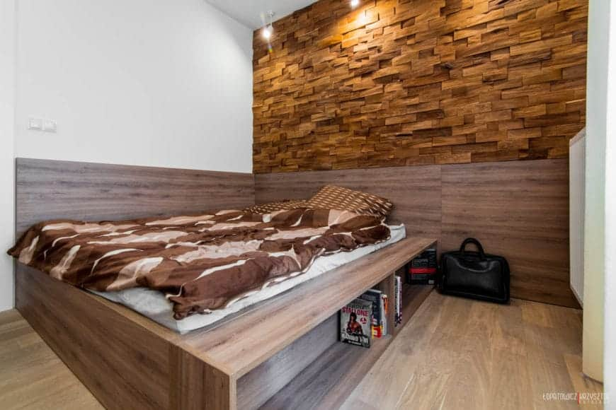 The bed cushion is on a wooden platform that extends to the middle part of the wall and has built-in shelves beneath it. The wall above the head of the bed is consisted entirely of wooden bricks fitted into the wall into a patterned texture that is comforting to look at.