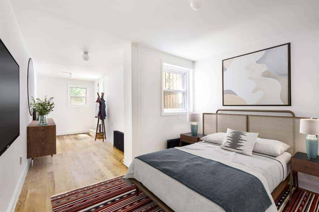 The simple lines and white walls of this Scandinavian-Style bedroom are counterbalanced by the colorful patterned area rug underneath the wooden bed. The bed is flanked by the identical wooden bedside table with a simple table lamp on it.