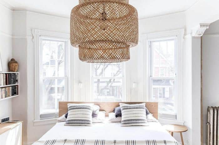 The rustic woven wicker covering of the pendant light hanging from the white ceiling is a good contrast for the white brightness of the room. This brightness is mostly due to the three windows behind the wooden headboard of the bed.