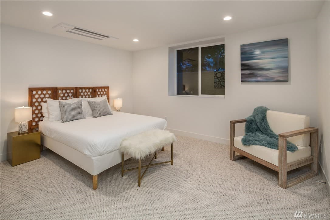 This is a boxy type of bedroom with its white walls and white ceiling. This monotony is broken by a lovely colorful painting mounted next to a window. The white bed is given a wooden patterned headboard flanked by golden bedside tables.