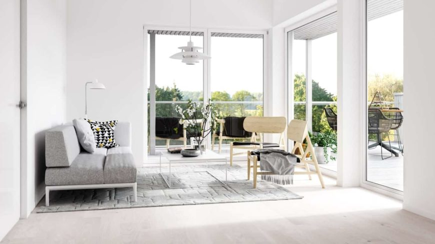 The simplicity of this Scandinavian-style living room is the source of its beauty complemented by the natural lights of the tall glass sliding doors and windows. The gray sofa and light wood chairs are a nice complement to the white walls and ceiling.
