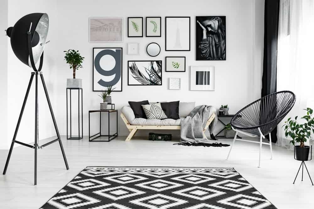The white wall of this Scandinavian-Style living room is filled with artistic and attractive wall decors.