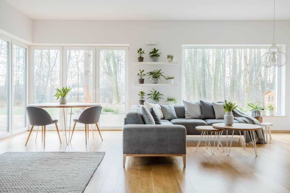 Large Scandinavian-Style living space featuring hardwood floors and white walls, along with a gray L-shape sofa set and a small coffee table set on the side.
