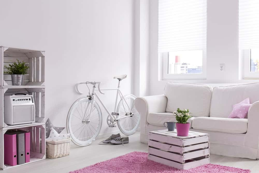 Scandinavian-Style living room with a pink shade. It features white walls and ceiling, along with a bicycle decor painted in white.