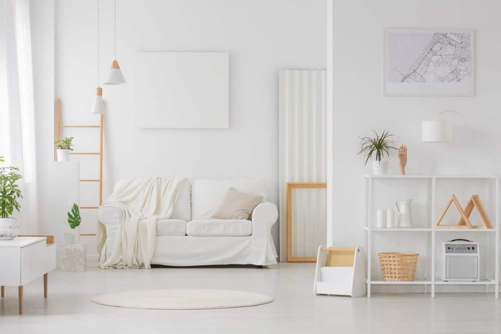 Scandinavian-Style living room featuring a white couch matching the white walls and white flooring. The room offers multiple indoor potted plants, adding color to the space.
