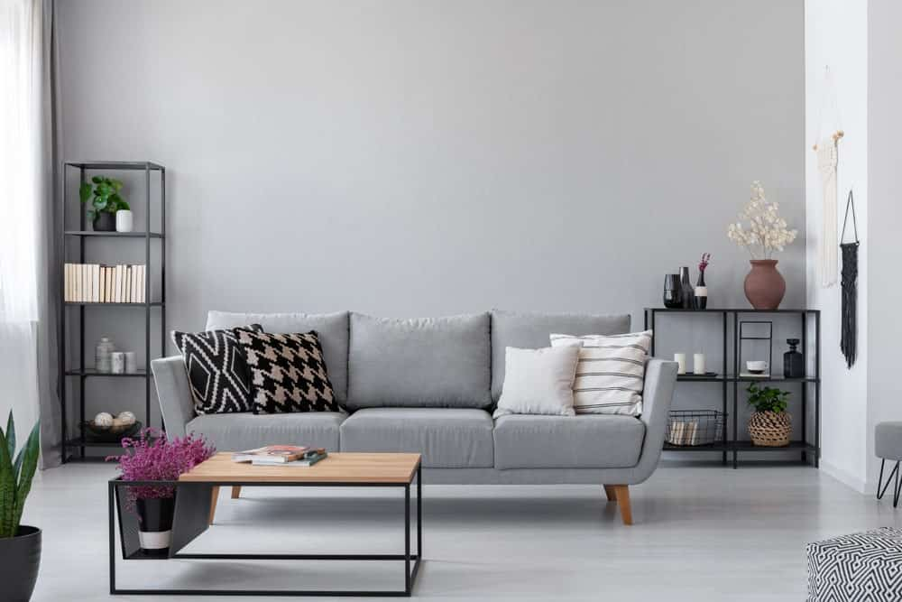Scandinavian-Style living room featuring a gray sofa matching the gray hardwood flooring and gray wall. The room also offers freestanding shelves.