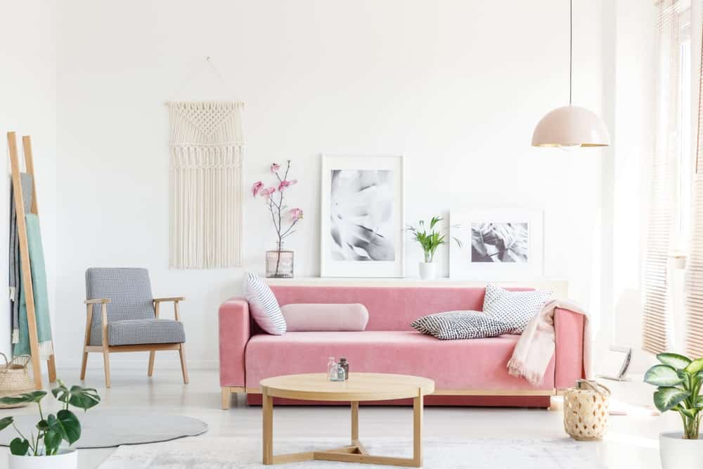 Scandinavian-Style living room surrounded by white walls and white flooring. It offers a pink couch and a gray seat on the side.
