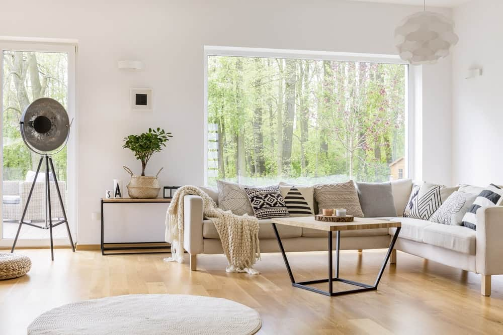 Scandinavian-Style living room featuring a white L-shape sofa set on top of the hardwood flooring. The center table looks very stylish as well.