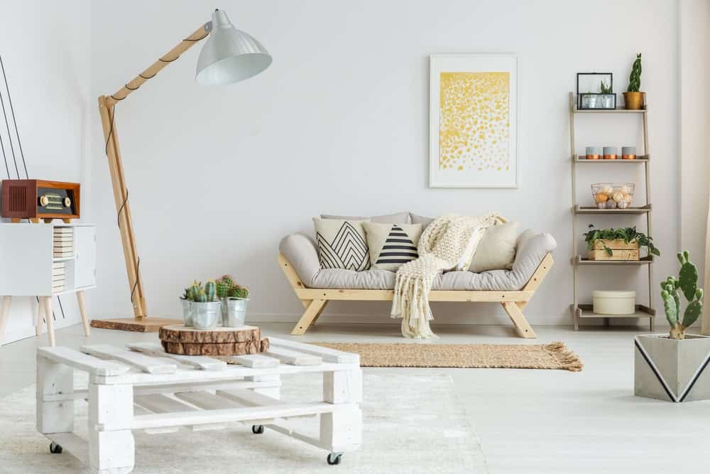 A bright Scandinavian-Style living room with its white walls and flooring. It also offers a lovely couch and freestanding shelving.