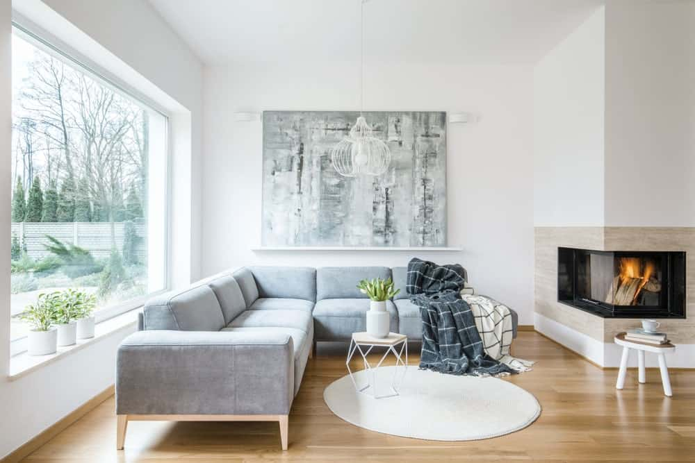 A Scandinavian-Style living space featuring a gray L-shape sofa set on the hardwood flooring near the glass windows. The room also offers a fireplace, along with attractive wall decor.