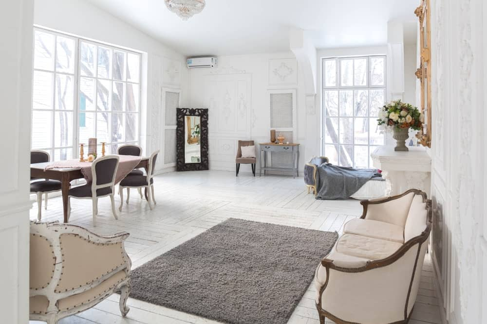 Spacious Scandinavian-Style living space featuring a classy set of seats and a rectangular dining table set on the side. The room offers hardwood flooring topped by a gray area rug.