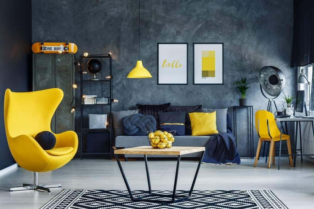 Scandinavian-Style formal living space featuring yellow seats and a gray couch set on the gray flooring, surrounded by stylish black and gray walls.