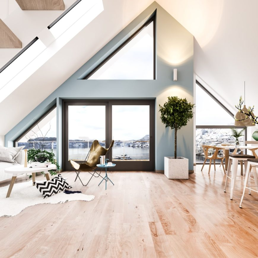 Large Scandinavian-Style living space featuring hardwood flooring and a stunning tall ceiling. The home features a gray and white shade for additional style.