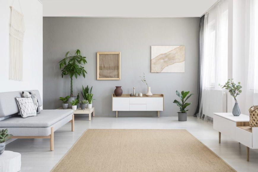 Spacious Scandinavian-Style living room featuring a gray seat and lovely side tables, along with a gray wall and multiple green potted plants.