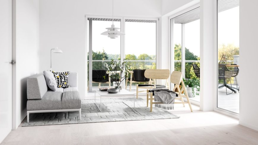 This Scandinavian-Style living room features a gray sofa set on top of a rug, surrounded by white walls and white ceiling.