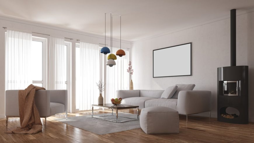Spacious Scandinavian-Style living room featuring a cozy sofa set with a center table lighted by pendant lights. The room also offers a fireplace.