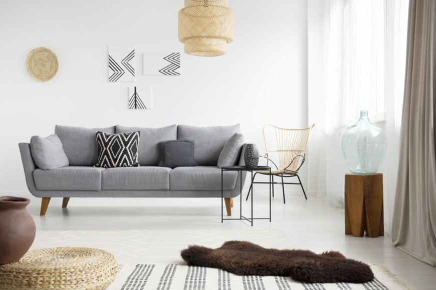This Scandinavian-Style living room looks so bright with its white walls and floors. It has a gray couch and stylish wall decors.
