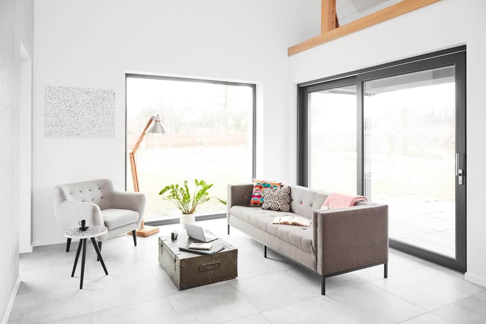 Small Scandinavian-Style living room featuring a cozy sofa set and gray flooring, along with a glass door and window.