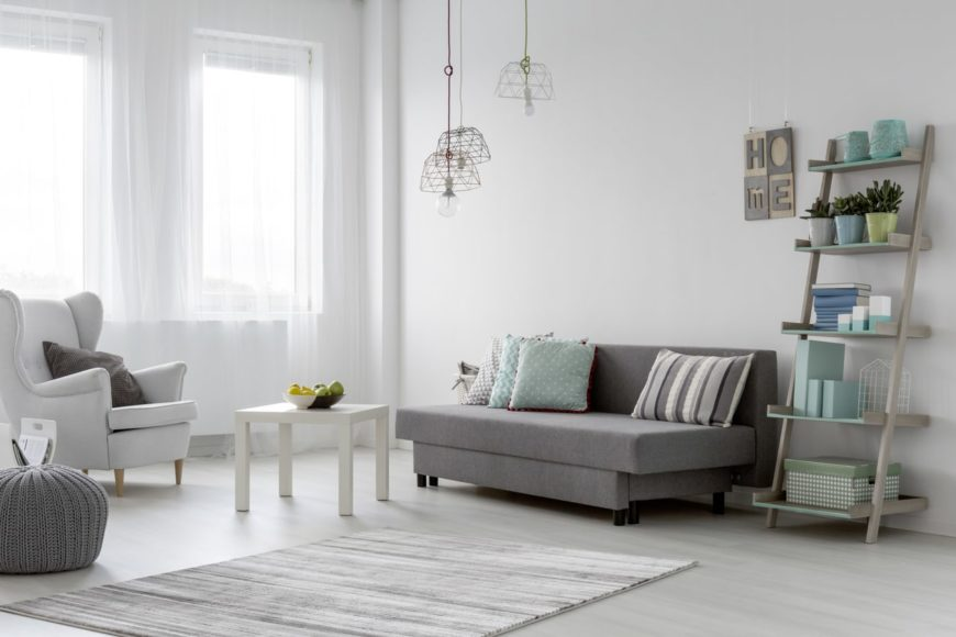 White Scandinavian-Style living room featuring a gray sofa set and gray hardwood flooring, along with a tall ceiling featuring pendant lights.