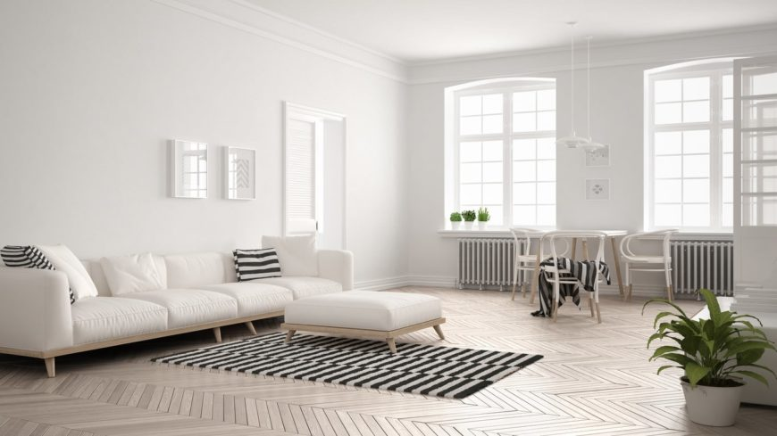 Large Scandinavian-Style formal living room featuring herringbone-style hardwood flooring, white walls and a white regular ceiling. The room also features a white sofa set.
