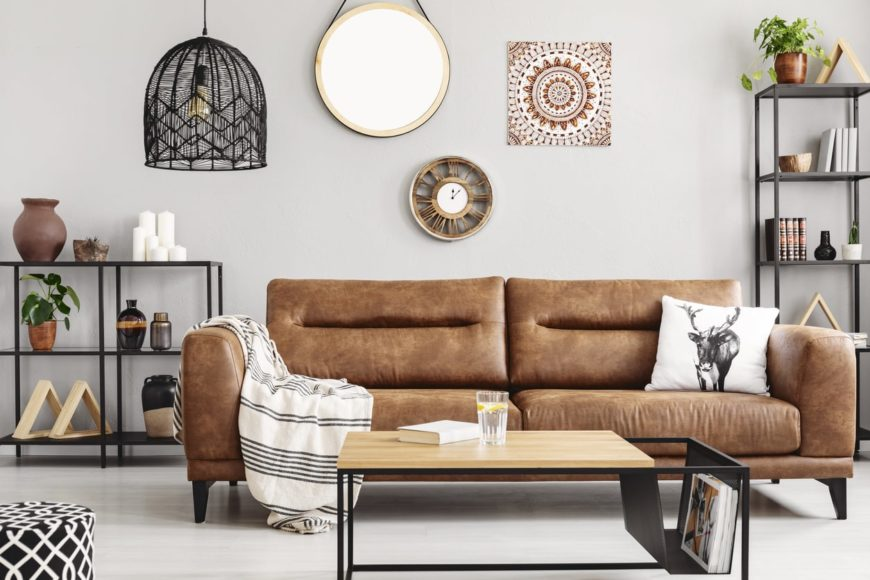 A close up look at this Scandinavian-Style living room's brown couch and a white wall with multiple attractive decors.