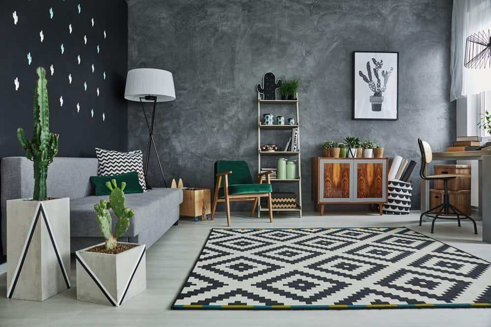 Scandinavian-Style living room featuring black and gray walls making the room look so handsome. It also features an office desk and a gray sofa set, along with a stylish rug covering the gray flooring.