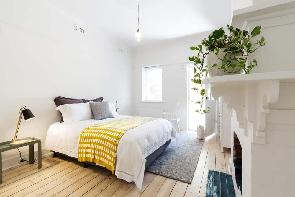 Small Scandinavian-Style master bedroom with white walls and ceiling along with the hardwood flooring topped by a gray rug. There's a fireplace keeping the place warm.