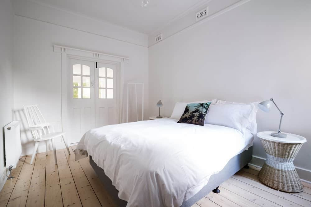White Scandinavian-Style master bedroom featuring a white chair on the corner and two stylish side tables set on the hardwood flooring.