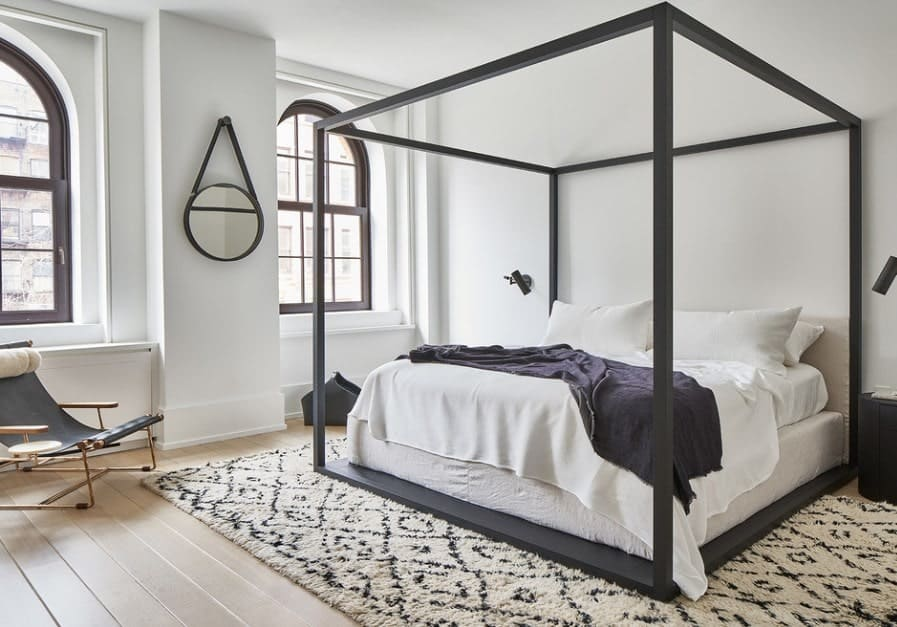 A modish Scandinavian-Style master bedroom with a stylish bed set and a handsome rug covering the hardwood flooring.