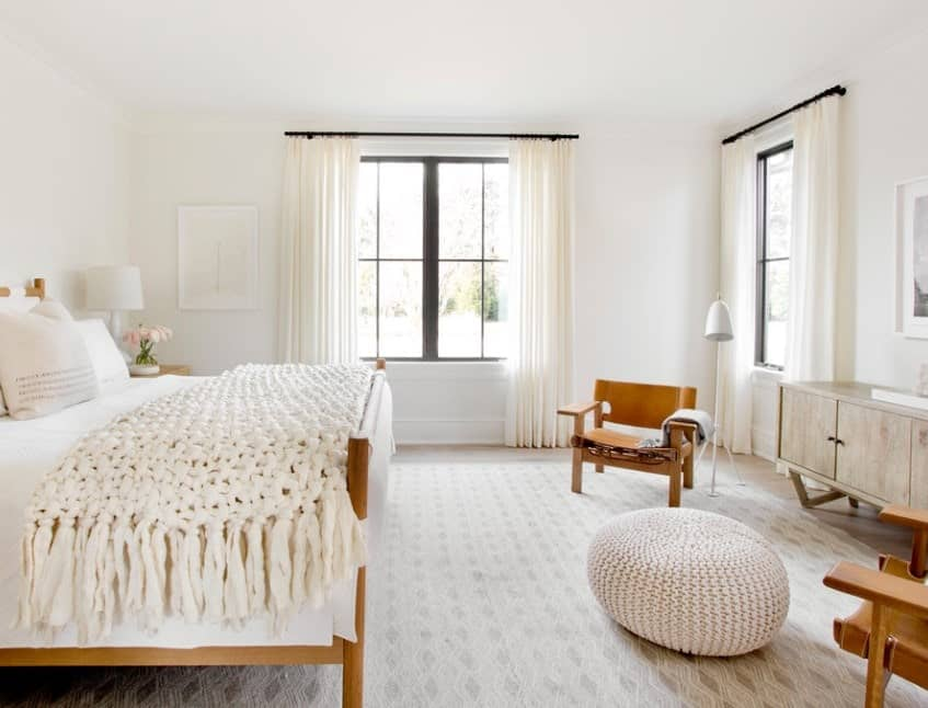 A classy Scandinavian-Style master bedroom with beautiful white window curtains matching the white classy rug and bed set.