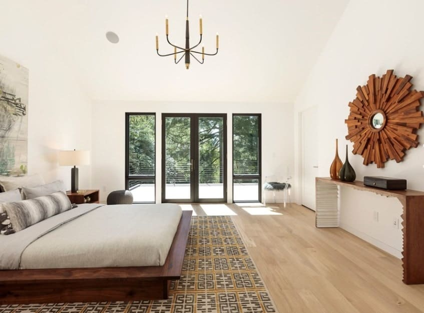 Large Scandinavian-Style master bedroom with a gorgeous chandelier lighting up the space. The bed looks classy together with the wall decors.