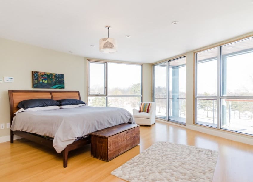 This Scandinavian-Style master bedroom features glass windows and hardwood floors. There's a private balcony as well, overlooking the great outdoor views.