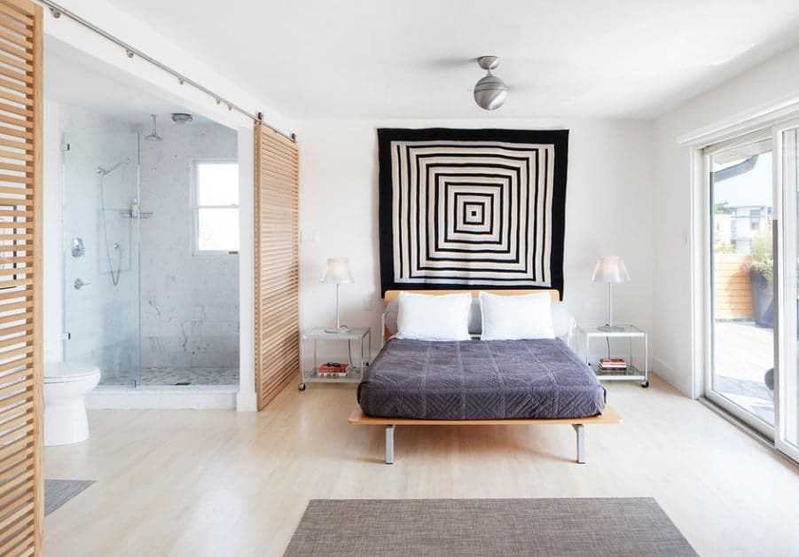 A spacious Scandinavian-Style master bedroom featuring sliding doors leading to the suite's bathroom.