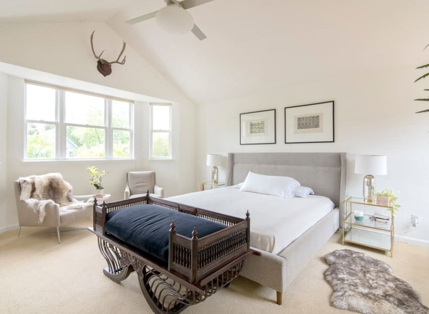 This Scandinavian-Style master bedroom boasts classy carpet flooring and a luxurious bed under the white vaulted ceiling.