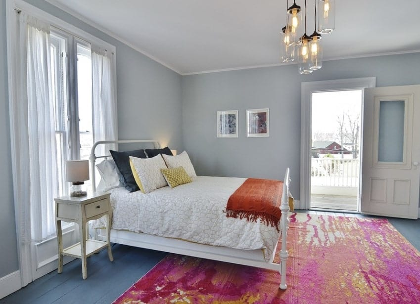 This Scandinavian-Style master bedroom boasts stylish blueish gray floors topped by a very attractive rug. The pendant lighting looks so elegant and charming.