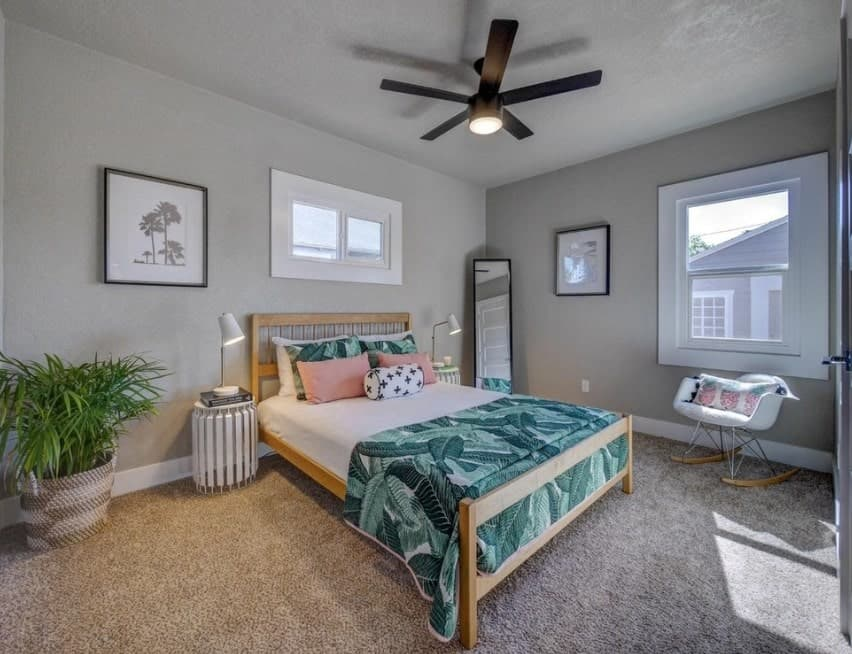 A stylish Scandinavian-Style master bedroom featuring cozy carpet flooring and handsome gray walls.