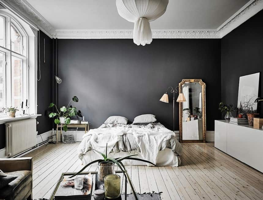 This Scandinavian-Style master bedroom boasts elegant black walls surrounding the room. The hardwood flooring adds charm to the area. The ceiling looks stunning as well.