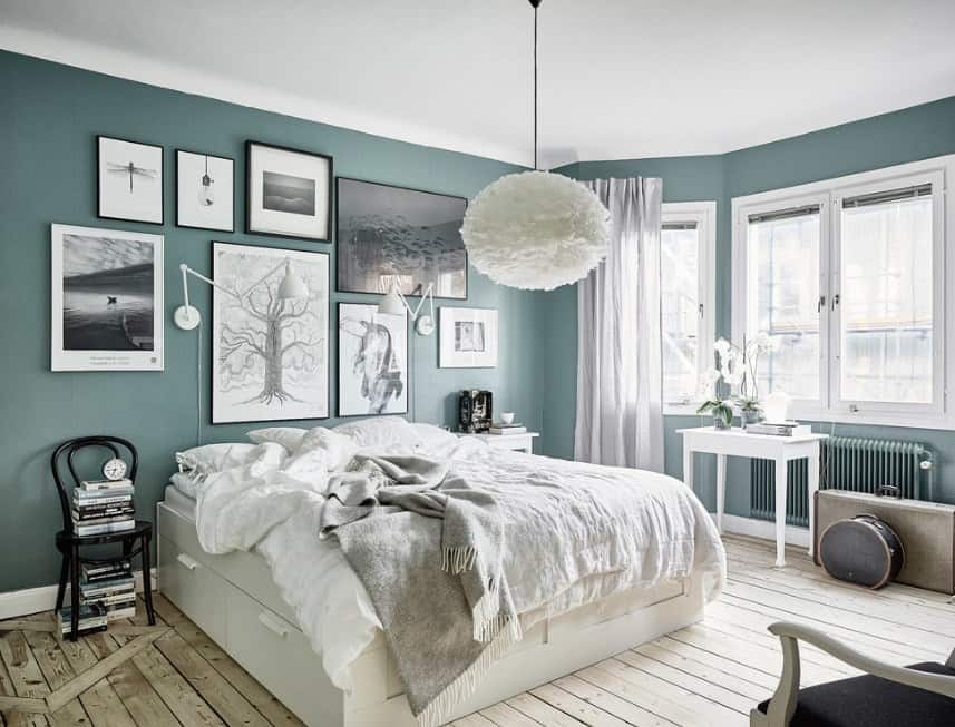 A very attractive Scandinavian-Style master bedroom with green walls decorated with multiple artistic wall decors. The ceiling lighting looks so charming as well.