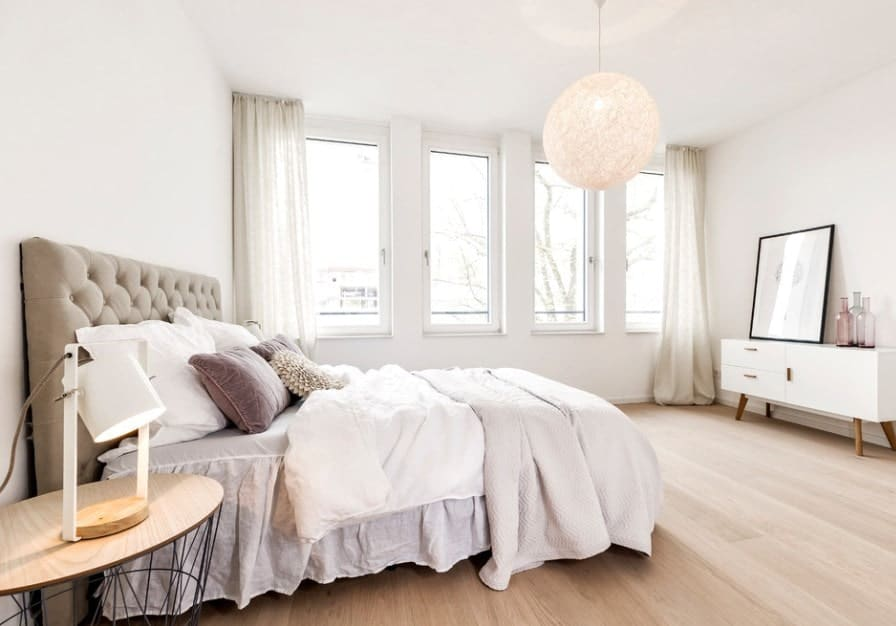 White Scandinavian-Style master bedroom with a stunning bed and classy white window curtains matching the white walls. The pendant light is just so glamorous.